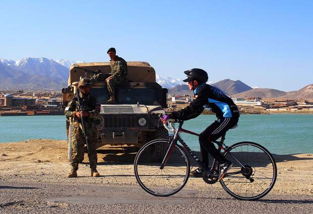 A member of the Afghan National Cycling team pedals past military personnel in Afghanistan.