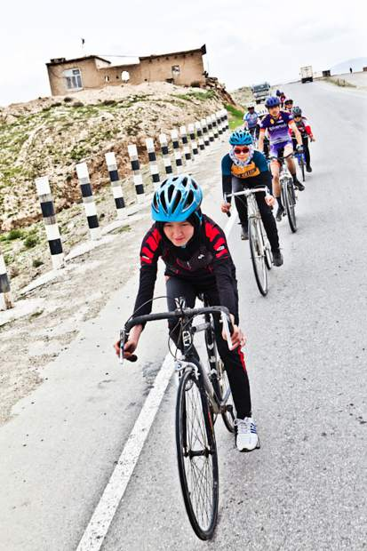 Members of the Afghan Women's National Cycling Team ride down a mountain highway in Afghanistan.