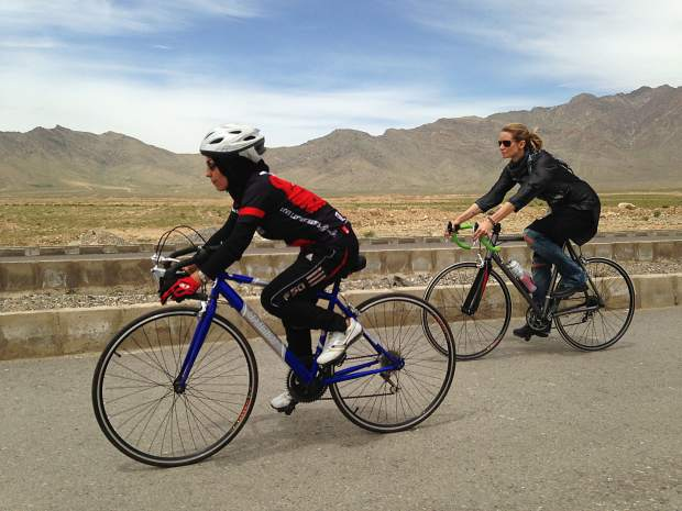Shannon Galpin (right) and an Afghan women ride their bicycles in Afghanistan.