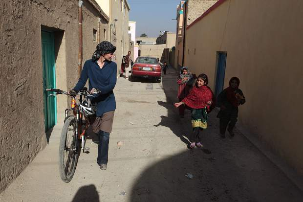 Afghan children follow Summit County local Shannon Galpin as she walks her bike through an alley in Afghanistan.
