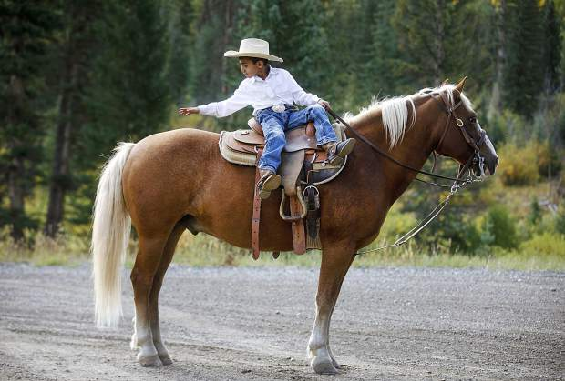 A young cowboy, Emiliano Mendiola, 6, pats his horse, Tommy, following the cattle drive between the two ranches on Highway 9 Tuesday, Sept. 11, north of Silverthorne.