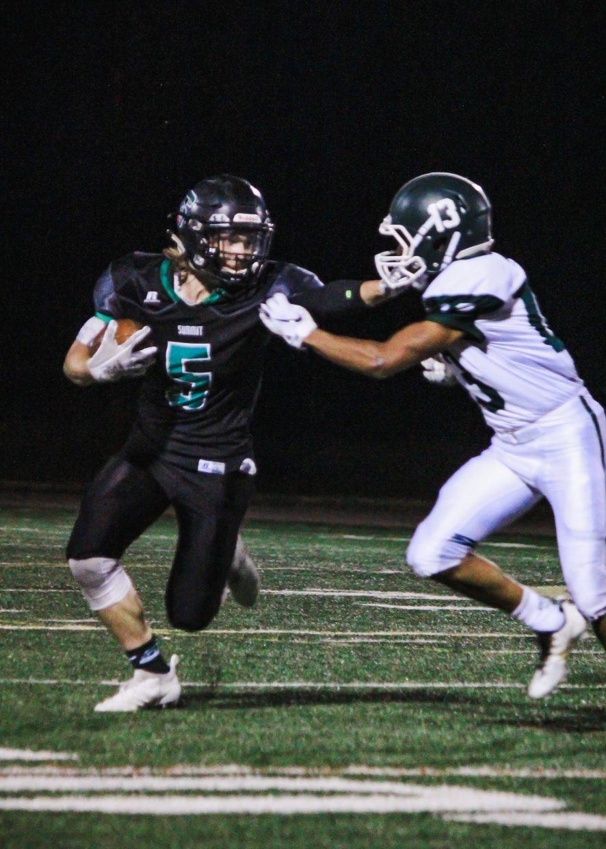 Summit Tigers sophomore running back Noah Martens stiff-arms a Woodland Park defender during Friday's 38-30 Tigers win.