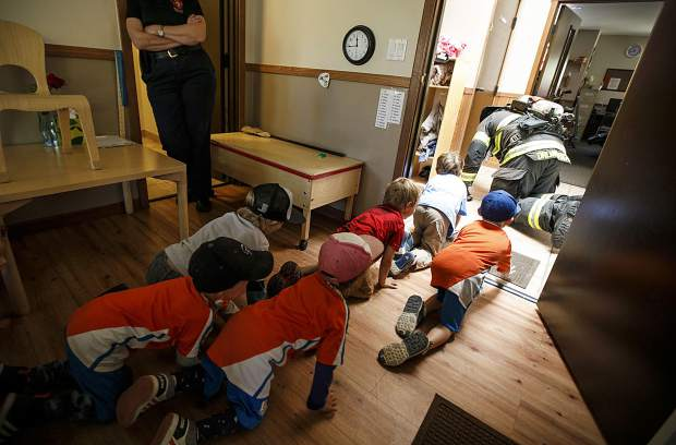 Students crawl while following Red, White, and Blue Firefighter Paramedic Chris Drumwright in a fire safety demonstration in class Thursday, Sept. 27, at Little Red SchoolHouse in Breckenridge.