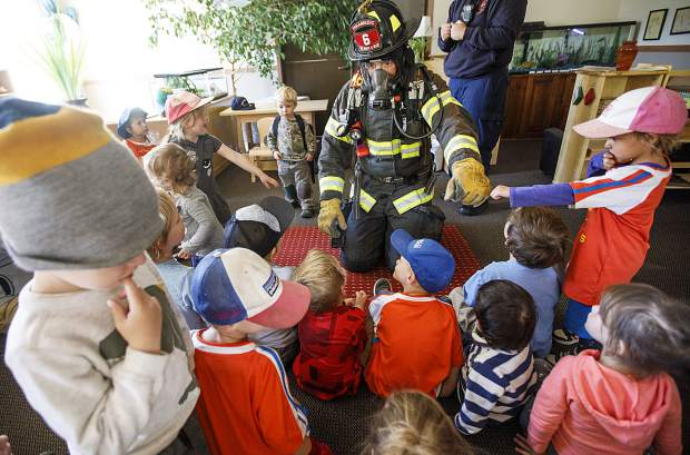 Pre-schoolers fist bump Red, White, and Blue Firefighter Paramedic Chris Drumwright to earn trust of firefighters in case of an emergency during class Thursday, Sept. 27, at Little Red SchoolHouse in Breckenridge.