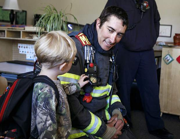 Red, White, and Blue Firefighter Paramedic Chris Drumwright smiles as a pre-school student check out his gear during class Thursday, Sept. 27, at Little Red SchoolHouse in Breckenridge.