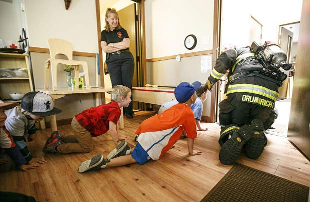 Red, White, and Blue Firefighter Paramedic Chris Drumwright demonstrates the crawling escape route for pre-school students during fire safety session in class Thursday, Sept. 27, at Little Red SchoolHouse in Breckenridge.