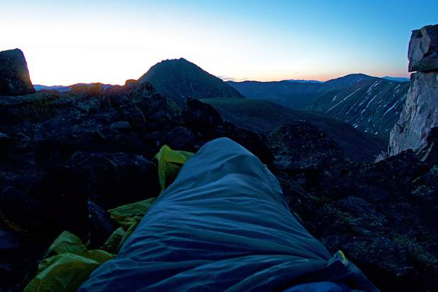 Justin Simoni, 37, of Boulder wakes to the sunrise in his bivy on the cliffside near Drift Peak during his four-plus day traverse from Trout Creek Pass near Buena Vista along the Mosquito and TenMile Ranges to Frisco.
