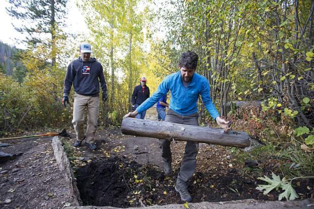 Summit Fat Tire Society vice president Ben Ferrante brings in a new log to improve Peaks Trail for better climbing and descending Thursday, Sept. 20, near Frisco.