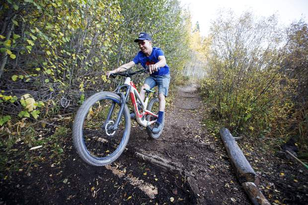 Volunteer Kris Karlsted test rides the upgraded log section of the Peaks Trail Thursday, Sept. 20, near Frisco.