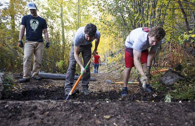 Volunteers Andy Demaline, left, and SFTS vice president Ben Ferrante, and Mike Olsen dig a fitting slot for the new log to make it accessible for beginner mountain bikers on the Peaks Trail Thursday, Sept. 20, near Frisco.