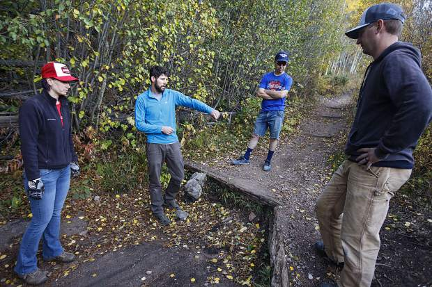Summit Fat Tire Society vice president Ben Ferrante, second from left, and the volunteers discuss improvement plans to make the log step portion of the trail for mountain bikers to descend and ascend more smoothly on the Peaks Trail Thursday, Sept. 20, near Frisco.