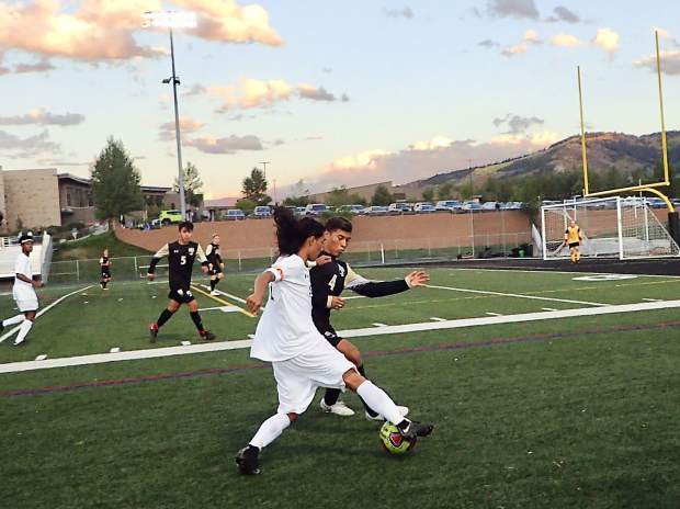 Summit Tigers senior forward Farid Infante attacks down the right flank versus Battle Mountain's Hidalgo Ortega during their game on Tuesday in Edwards. Ortega scored the Huskies' third goal in their 4-0 win over the Tigers.