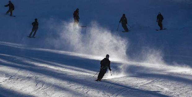 Skiers and snowboards make some of the first runs of the season on opening day at Arapahoe Basin Ski Area on Friday.