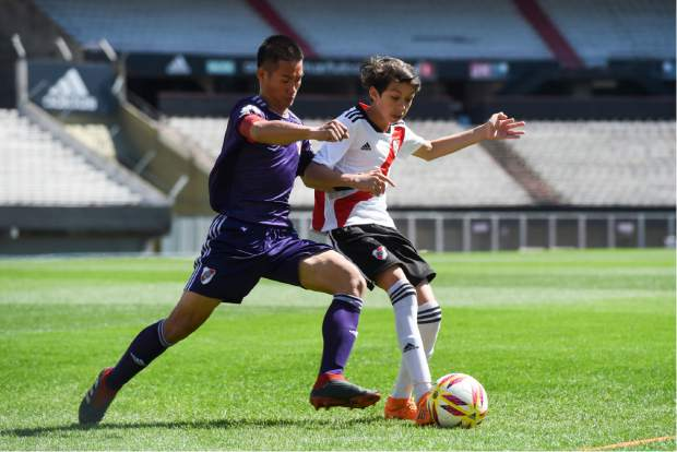 Kapol Jantawong, coach and captain of Thai team Wild Boars, left, fights for the ball during a friendly soccer match against River Plate Youth Team at Monumental stadium in Buenos Aires, Argentina on Sunday. The team made up of 12 boys and their coach, who were trapped in a flooded cave for almost three weeks in Thailand, are guests in Buenos Aires during the opening days of the Youth Olympic games.