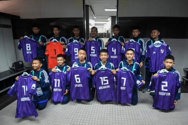 Young soccer Thai team Wild Boars pose for a group photo in the changing room of River Plate's Monumental stadium before a match against a local junior team, on the sidelines of the Youth Olympic Games in Buenos Aires, Argentina on Sunday. The team made up of 12 boys and their coach, who were rescued from a cave in Thailand, played a friendly match against the youth team of River Plate on Sunday.