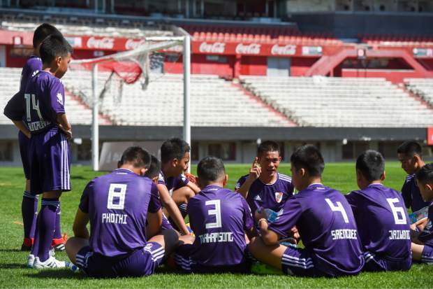 Kapol Jantawong, center, coach and captain of Thai team Wild Boars, gives instructions during a friendly soccer match against River Plate Youth Team at Monumental stadium on the sidelines of the Youth Olympic Games in Buenos Aires, Argentina, Sunday, Oct. 7, 2018. The team made up of 12 boys and their coach, who were rescued from a cave in Thailand, played a friendly match against the youth team of River Plate Sunday.