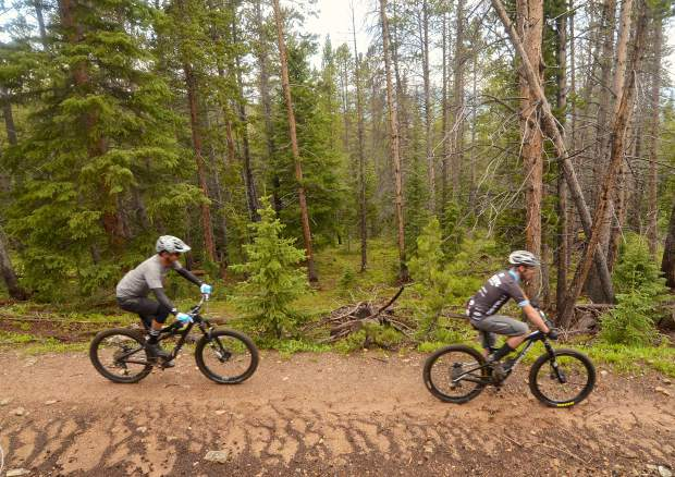 Breckenridge mountain biker Matt Powers (right) and former Boulder pro Paul Wells pedal along a stretch of wooded doubletrack on the Weber Gulch trail during a lunch loop led by Breck mayor Eric Mamula — Powers' brother-in-law and Wells' friend of 25-plus years.
