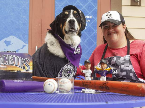 Summit Daily News assistant managing editor and lifeling Colorado Rockies fan Susan Gilmore poses for a photo with some of her favorite Colorado Rockies mementos alongside her pup Charlie. Earlier this summer, Charlie -- who's wearing a 1993 Rockies inaugural season T-shirt in this photo -- led the