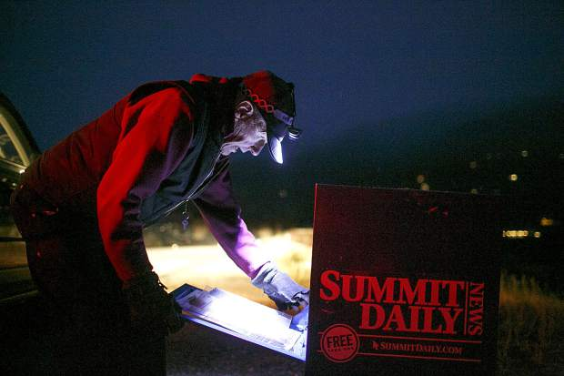 Jack Mathews delivers fills a box with a stack of papers during the early hours of Thursday, Oct. 11, in Silverthorne.