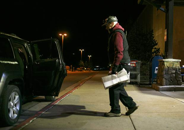 Jack Mathews picks up stacks of the Summit Daily News in Dillon to load into his own car for delivery in Silverthorne, Thursday, Oct. 11.