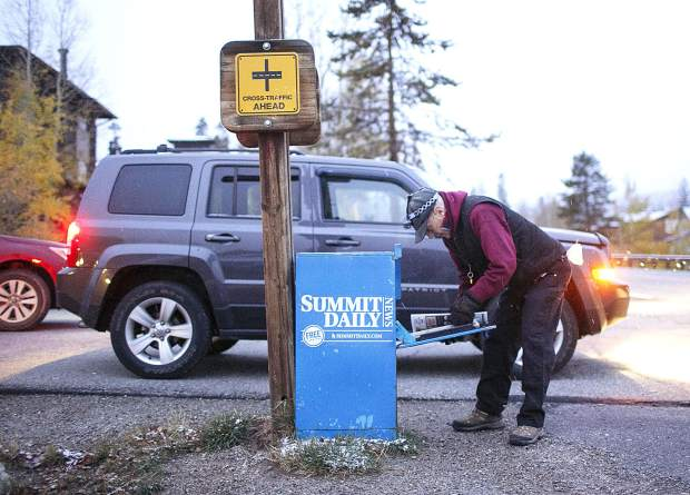 Jack Mathews delivers the day's edition in the Summit Daily News' newspaper vending box Thursday morning, Oct. 11, in the wildernest neighborhood of Silverthorne.
