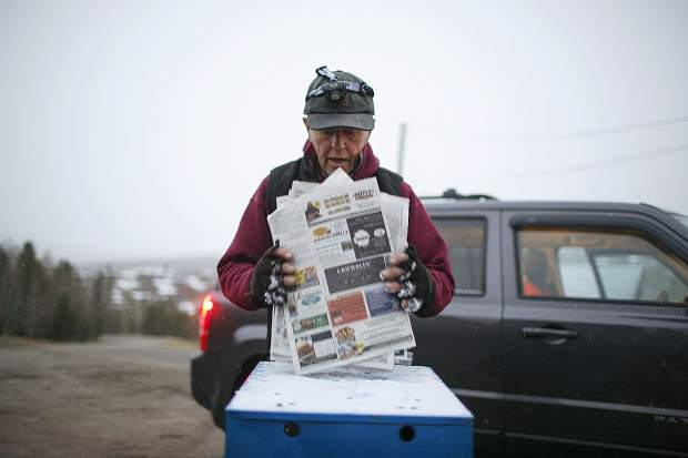 Jack Mathews cleans out the previous day's edition in the Summit Daily News' and the advertising papers from a vending box in the early hours of Thursday, Oct. 11, in the wildernest neighborhood of Silverthorne.