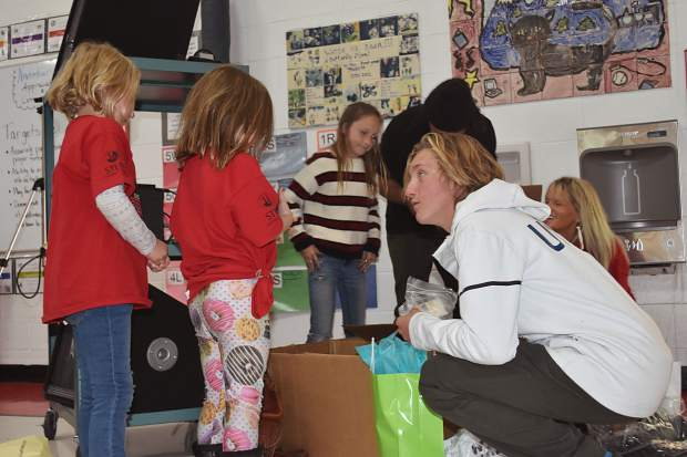 Olympic gold-medal winning snowboarder Red Gerard reaches into his bag of sponsor goodies while his sister and Frisco Elementary fourth-grader Asher (rear center) helps her brother out during his return to his old school, Frisco Elementary, on Tuesday afternoon.