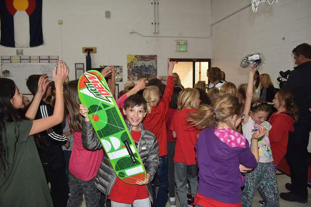 A Frisco Elementary School student holds up the Mountain Dew skateboard he was given by Olympic gold-medal winning snowboarder Red Gerard during Gerard's visit to his former school on Tuesday afternoon.