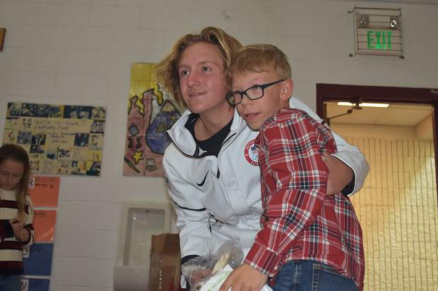 Olympic gold-medal winning snowboarder Red Gerard poses for a photo with a Frisco Elementary School student, his younger sister Asher Gerard in view at rear, during Red Gerard's return to his former school on Tuesday afternoon.