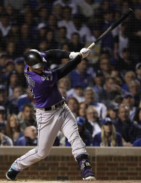 Colorado Rockies' Nolan Arenado hits a sacrifice fly against the Chicago Cubs during the first inning of the National League wild-card playoff baseball game Tuesday, Oct. 2, 2018, in Chicago.