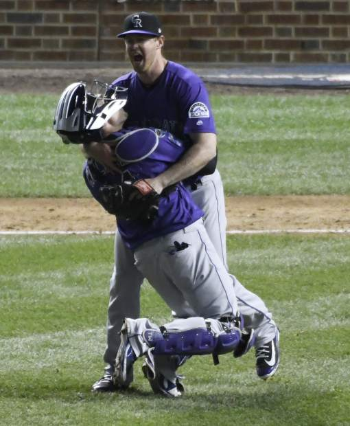 Colorado Rockies catcher Tony Wolters, front, and Colorado Rockies relief pitcher Scott Oberg, rear, celebrate their win in the National League wild-card playoff baseball game on Wednesday in Chicago. The Rockies won 2-1 in thirteen innings.