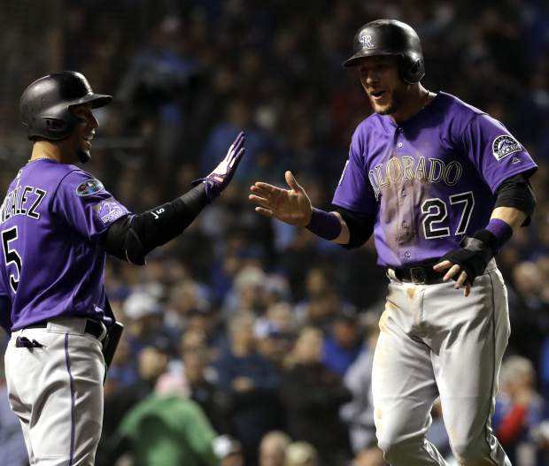 Colorado Rockies' Trevor Story, right, celebrates with Carlos Gonzalez after scoring on a one-run single by Tony Wolters during the 13th inning of the National League wild-card playoff baseball game against the Chicago Cubs, Tuesday, Oct. 2, 2018, in Chicago.
