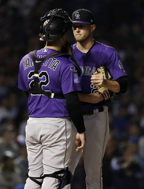 Colorado Rockies starting pitcher Kyle Freeland, right, talks with catcher Chris Iannetta during the sixth inning of the National League wild-card playoff baseball game against the Chicago Cubs, Tuesday, Oct. 2, 2018, in Chicago.