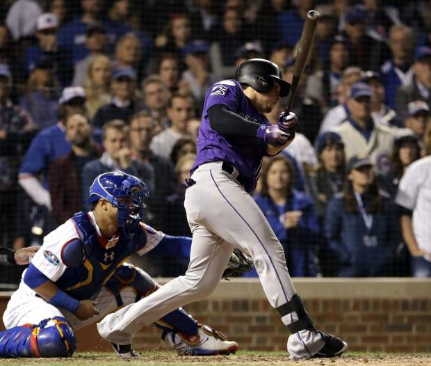 The Colorado Rockies' Tony Wolters hits a one-run single against the Chicago Cubs during the 13th inning of the National League wild-card playoff baseball game on Tuesday in Chicago.