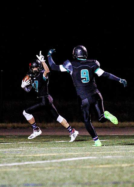 Summit senior wide receiver Angel Arrendondo motions to teammate Daniel Gonzalez en route to his 40-yard-plus touchdown reception early the first quarter of Friday night's 20-7 home victory versus Eagle Valley at Tiger Stadium.
