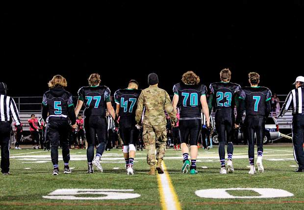 Summit High School football varsity team captains walk hand-in-hand with honorary Salute to Service game captain and Flight For Life Helicopter nurse Dave Repsher at the start of Friday night's 20-7 win versus Eagle Valley.