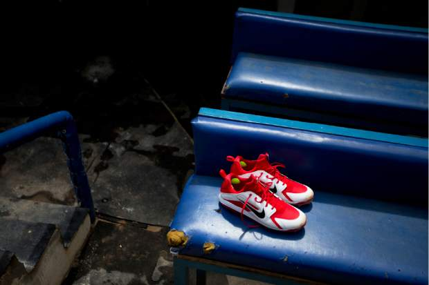 A pair of new baseball shoes sit on a worn-out bench in the Los Tiburones de la Guaira's dugout prior the season's opening game on Friday against Leones de Caracas in Caracas, Venezuela. Venezuela's once highly competitive winter league has been in decline for years and major league organizations have shut down all their academies in the country.
