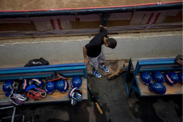 A stadium worker adjusts floor mats in the dugout of the Tiburones de La Guiara team prior to the baseball season's opening game between Leones de Caracas and Tiburones de la Guaira in Caracas, Venezuela on Friday. During the offseason, vandals picked through stadiums across the country; groundskeepers have been battling water shortages; and ticket prices remain a mystery, with most clubs changing them by the week to keep pace with inflation soon to reach 10 million percent.