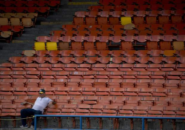 A lone baseball fan waits for the season's opening baseball game between Leones de Caracas and Tiburones de la Guaira in Caracas, Venezuela on Friday. Some baseball fans avoid the ballpark for fear of getting mugged or because they don't know how they'll get home amid a nationwide transportation crisis.