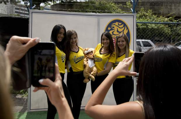 Leones de Caracas cheerleaders pose for a photo with a young fan wearing a lion costume prior to the season's opening baseball game between Leones de Caracas and Tiburones de la Guaira in Caracas, Venezuela on Friday. From field crews to ticket scalpers to hot dog vendors to cheerleaders, thousands of families depend on baseball to make a living.