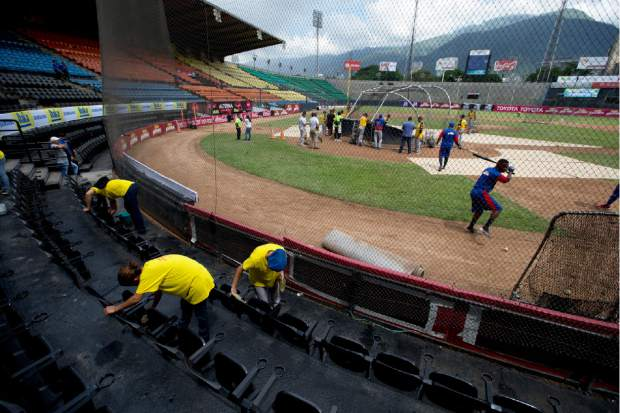 Workers clean the VIP seating area prior to the baseball season's opening game between Leones de Caracas and Tiburones de la Guaira in Caracas, Venezuela on Friday. Ramon Guillermo Aveledo, a former Venezuela baseball league president and prominent opposition leader, said he applauds the government's decision to spend its dwindling supply of dollars on baseball while acknowledging there are more pressing needs.