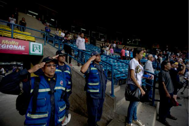 Firefighters salute during the national anthem at the start of the baseball season's opening game between Leones de Caracas and Tiburones de la Guaira in Caracas, Venezuela on Friday. Baseball stadiums have served as a sporting sanctuary where fans of all classes and political backgrounds can set aside their differences and mounting hardships, said Ramon Guillermo Aveledo, a former Venezuela baseball league president and prominent opposition leader.