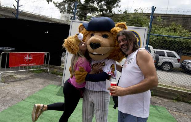 Baseball fans of Leones de Caracas pose with the team's mascot prior to the season's opening game against the Tiburones de la Guaira in Caracas, Venezuela. Last year's stadium attendance rose 5 percent amid the political and economic crisis, although it remains down by a third from a peak in the 2013-2014 season.