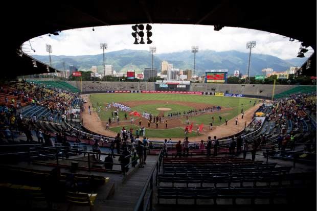 Baseball players and fans stand for the national anthem during the opening season baseball game on Friday between Leones de Caracas and Tiburones de la Guaira in Caracas, Venezuela. For the second straight year, state-run oil company PDVSA had to step in with a $12 million lifeline to pay for everything from imported baseballs to the salaries of seven foreign-born players -- most of them minor league prospects from the U.S. -- on each team's roster.