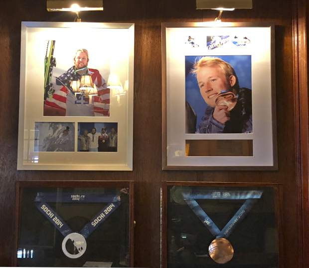 In this Sept. 1, 2018, photo, Olympic silver and bronze medals won by former U.S. skier Andrew Weibrecht hang behind the front desk of the Mirror Lake Inn in Lake Placid, New York.