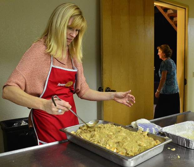 Rotarians work in the kitchen as even organizer Wendy Myers, right, keeps an eye on the room during the Summit County Rotary Community Thanksgiving Dinner at the Silverthorne Pavilion on Thursday.