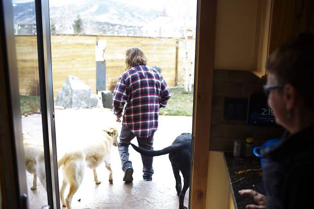 Dave Repsher heads out the backyard with, Turq, left, and Tucker, Saturday, Nov. 17, at home in Silverthorne.