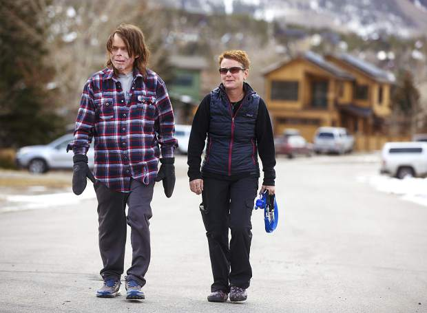 Flight For Life helicopter crash survivor Dave Repsher, left, and his wife, Amanda, chat while on a walk with their dogs Saturday, Nov. 17, near their home in Silverthorne. Dave sustained full-thickness burns on 90 percent of his body in the July 2015 helicopter crash.