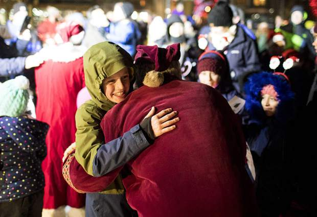 Santa Claus receives a hug from a fan at the Burning Stones Plaza in Center Village Friday, Nov. 23, at Copper Mountain.