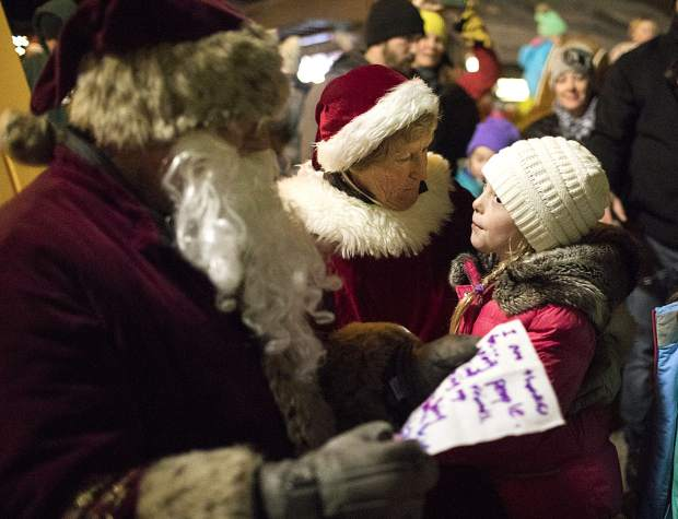 Santa and Mrs. Claus listens to a young wisher at the Burning Stones Plaza in Center Village Friday, Nov. 23, at Copper Mountain.